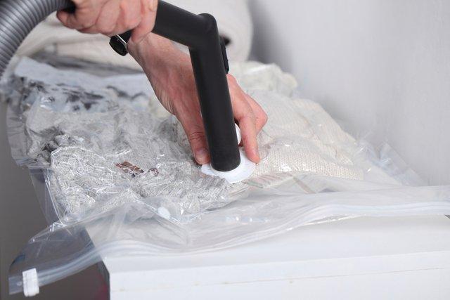 圧縮袋を掃除機で圧縮する男性の手