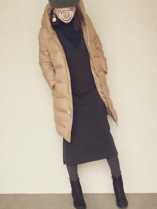 グレーのワンピースにキャメルのコートを着た女性