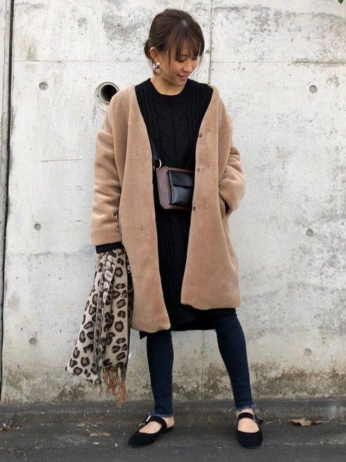黒コーデにキャメルのコートを羽織った女性