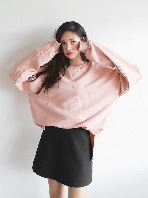 ピンクのパーカーに黒いスカートを穿いた女性