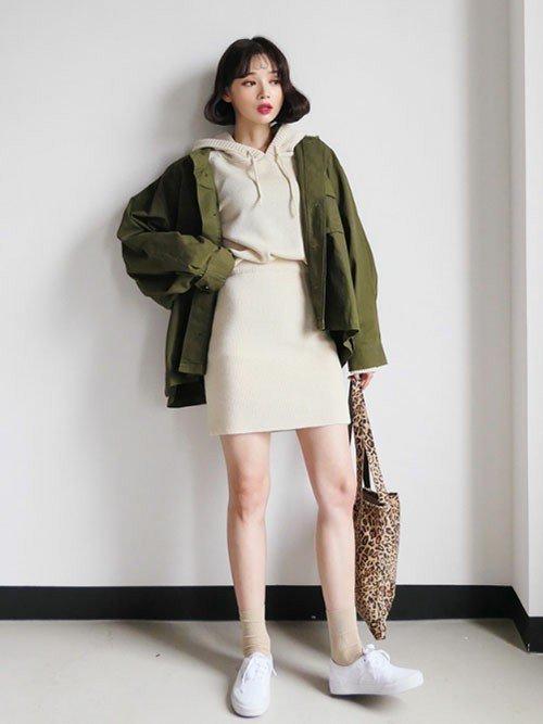 ベージュの服にカーキのジャケットを羽織った女性