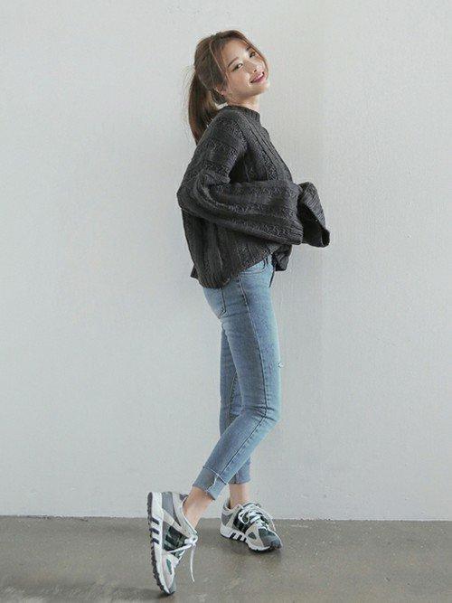 グレーのセーターにスキニーデニムを穿いた女性