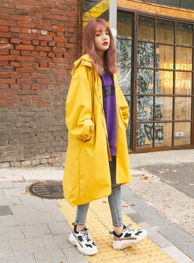 イエローのフード付ロングコートでスポーティミックスの雨の日コーデ