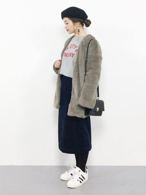 紺のタイトスカートにムートンコートを着た女性