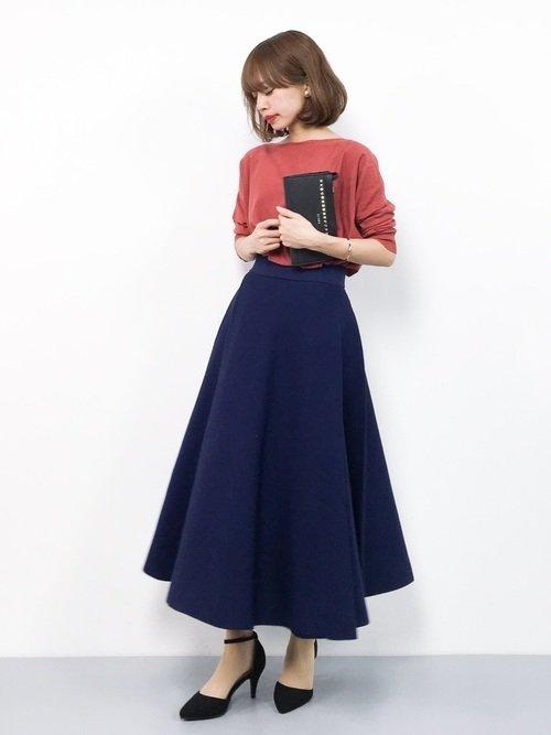 紺のスカートとピンクのニットを着た女性