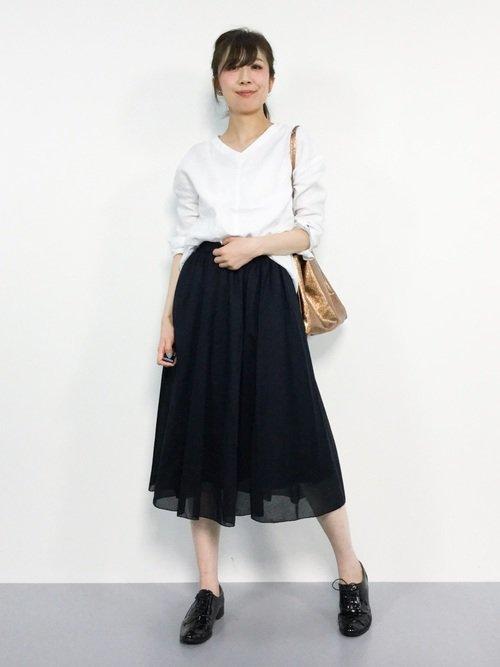 紺のフレアスカートと白いトップスを着た女性  紺のフレアスカートと白いトップスを着た女性  紺のフレアスカートと白いトップスを着た女性