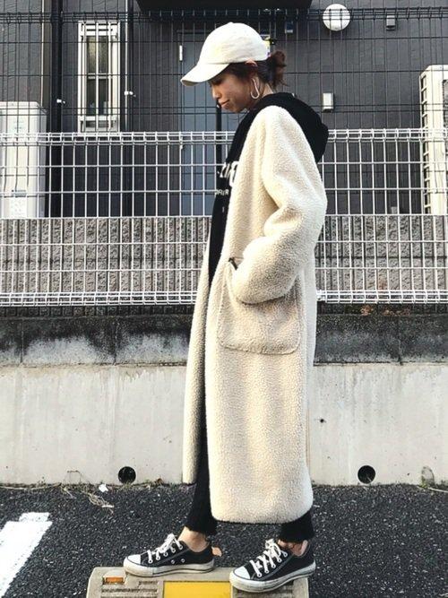 白のロングコートを着た女性