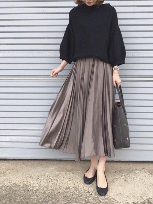 黒いトップスにベージュのスカートを穿いた女性