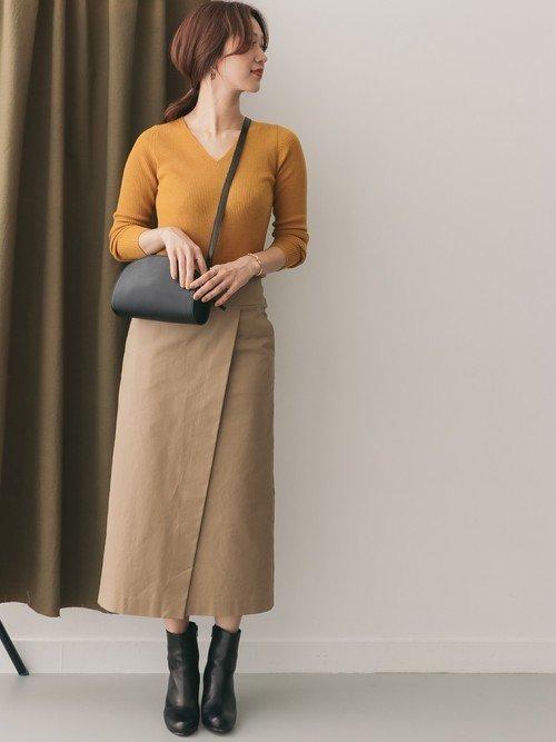 イエローのニットにタイトスカートを穿いた女性
