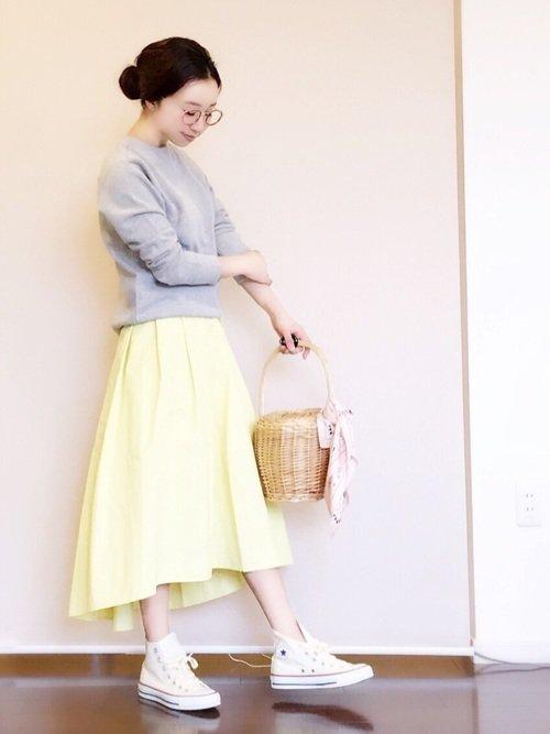 グレーのトレーナーに黄色いスカートを穿いた女性
