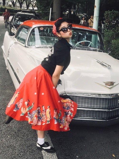 黒いトップスに赤いスカートを穿いた女性