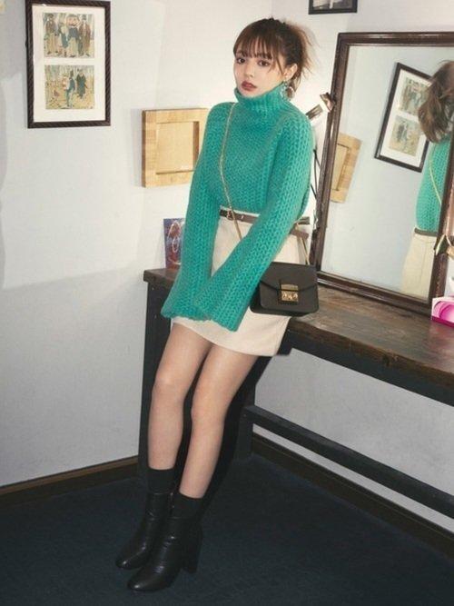 緑のニットとベージュのスカートのコーデ