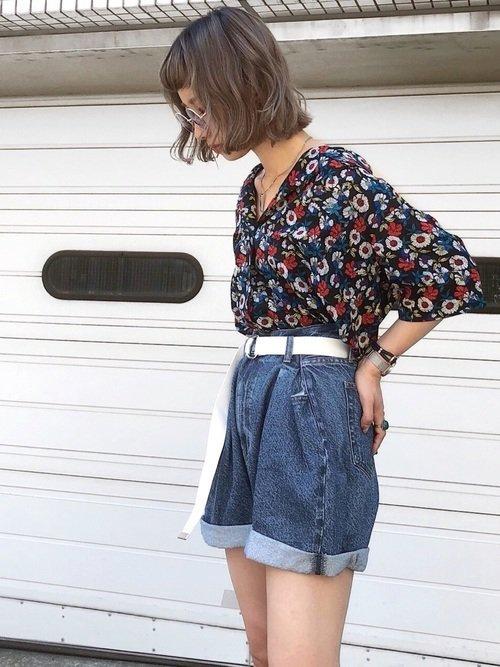 花柄トップスにショートパンツを穿いた女性
