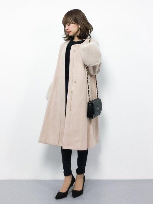 黒コーデにくすみピンクのコートを着た女性