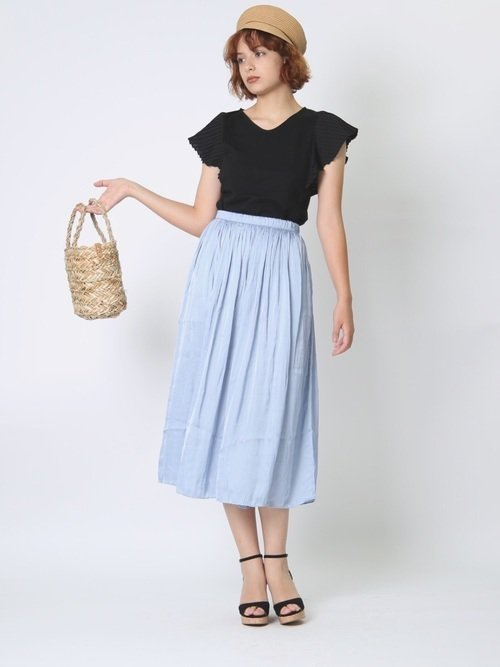 黒のトップスにブルーのスカートを穿いた女性