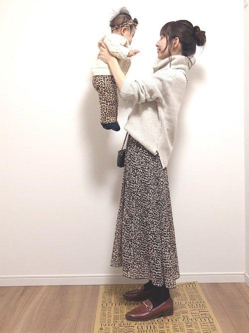 ニットにレオパード柄のボトムスを穿いた赤ちゃんと女性