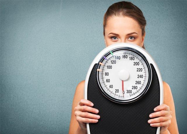 体重計を持った女性