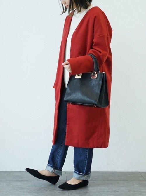 赤いノーカラーコートを着た女性
