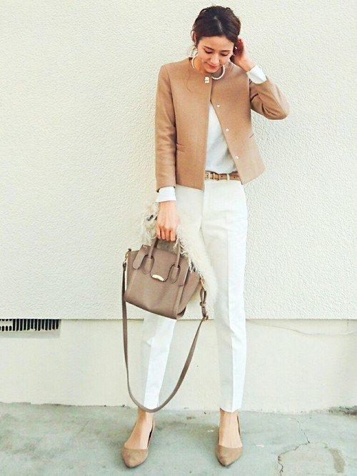 ベージュのジャケットに白いパンツを穿いた女性