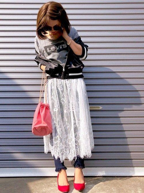黒のスカジャンにレーススカートを穿いた女性