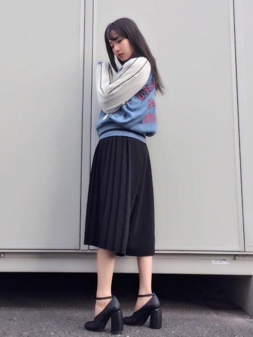 水色のスカジャンに黒のプリーツスカートを穿いた女性